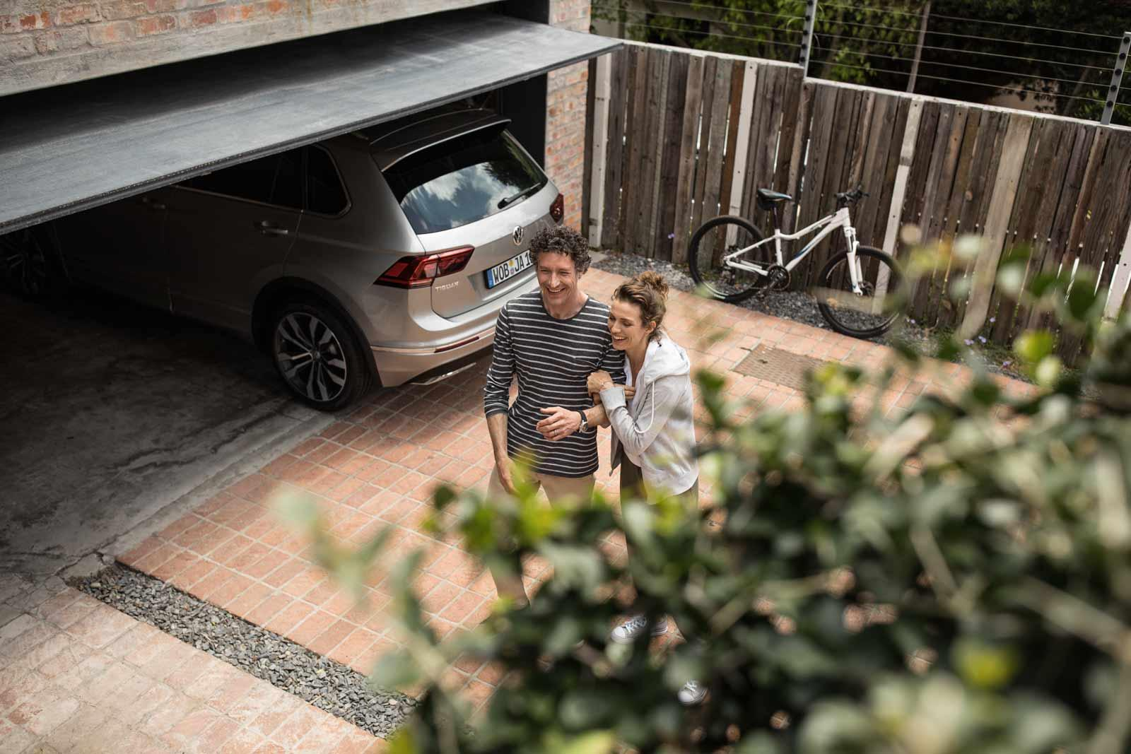 couple-standing-next-to-car-garage-laughing